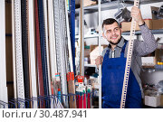 Купить «Smiling workman inspecting plastic trim corners», фото № 30487941, снято 15 марта 2017 г. (c) Яков Филимонов / Фотобанк Лори