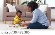 Купить «mother and baby playing with toy blocks at home», видеоролик № 30488385, снято 24 марта 2019 г. (c) Syda Productions / Фотобанк Лори
