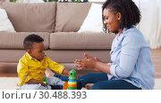 Купить «mother and baby playing with toy blocks at home», видеоролик № 30488393, снято 24 марта 2019 г. (c) Syda Productions / Фотобанк Лори