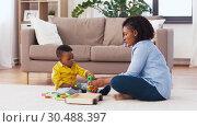 Купить «mother and baby playing with toy blocks at home», видеоролик № 30488397, снято 24 марта 2019 г. (c) Syda Productions / Фотобанк Лори