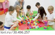 Купить «Happy kids and female teacher playing together with colorful toy building blocks in classroom at elementary school», видеоролик № 30496257, снято 18 декабря 2018 г. (c) Яков Филимонов / Фотобанк Лори