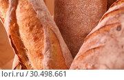 Купить «Breads and other bakery in decorative basket in background close up slow motion medium shot in 4K», видеоролик № 30498661, снято 5 ноября 2018 г. (c) Uladzimir Sitkouski / Фотобанк Лори