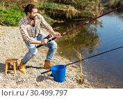 Купить «Adult man standing near river and pulling fish expressing emotions of dedication», фото № 30499797, снято 15 марта 2019 г. (c) Яков Филимонов / Фотобанк Лори