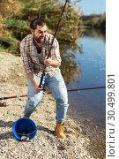 Купить «Adult man standing near river and pulling fish expressing emotions of dedication», фото № 30499801, снято 15 марта 2019 г. (c) Яков Филимонов / Фотобанк Лори