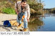 Купить «Adult man standing near river and pulling fish expressing emotions of dedication», фото № 30499805, снято 15 марта 2019 г. (c) Яков Филимонов / Фотобанк Лори