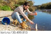 Купить «Positive fisherman holding catch freshwater fish in hands», фото № 30499813, снято 15 марта 2019 г. (c) Яков Филимонов / Фотобанк Лори