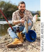 Купить «Bearded adult man posing with fish near river in summertime», фото № 30499821, снято 15 марта 2019 г. (c) Яков Филимонов / Фотобанк Лори