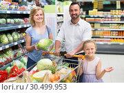 Купить «Smiling parents with child choosing lettuce», фото № 30499953, снято 21 августа 2019 г. (c) Яков Филимонов / Фотобанк Лори