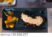 Купить «Tasty veal steak with pepper sauce and baked potatoes at plate», фото № 30500077, снято 19 апреля 2019 г. (c) Яков Филимонов / Фотобанк Лори