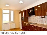Купить «Помещение кухни со встроенной мебелью и балконной дверью», фото № 30501953, снято 6 апреля 2019 г. (c) Ирина Борсученко / Фотобанк Лори