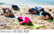 Купить «Sporty people practicing yoga on beach», фото № 30502429, снято 14 июня 2017 г. (c) Яков Филимонов / Фотобанк Лори