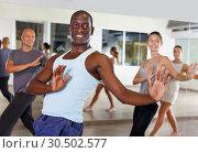 Купить «Cheerful people practicing vigorous lindy hop movements in dance class», фото № 30502577, снято 30 июля 2018 г. (c) Яков Филимонов / Фотобанк Лори