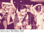Купить «Young bearded male is drinking cocktail», фото № 30502729, снято 2 августа 2017 г. (c) Яков Филимонов / Фотобанк Лори