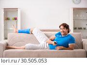 Купить «Leg injured young man on the sofa», фото № 30505053, снято 19 сентября 2018 г. (c) Elnur / Фотобанк Лори