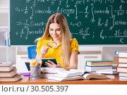 Купить «Young female student in front of the chalkboard», фото № 30505397, снято 18 октября 2018 г. (c) Elnur / Фотобанк Лори