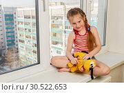 Купить «Russia, Samara, March 2017: A little girl is sitting with a plush dog on the windowsill of a high-rise building. Danger.», фото № 30522653, снято 14 марта 2017 г. (c) Акиньшин Владимир / Фотобанк Лори