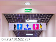 Купить «Light pointer Exit and signboard Toilet in the mall. Text in Russian: toilet exit», фото № 30522737, снято 23 февраля 2019 г. (c) Акиньшин Владимир / Фотобанк Лори
