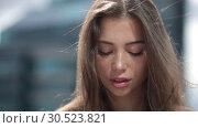 Купить «Portrait of a beautiful young woman, the wind blows hair.», видеоролик № 30523821, снято 4 апреля 2019 г. (c) Женя Канашкин / Фотобанк Лори