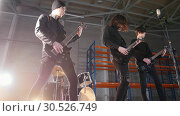 A rock group having a repetition. Guitarists in black clothes playing their parts and drummer on the background. Стоковое фото, фотограф Константин Шишкин / Фотобанк Лори