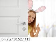 Купить «happy girl with easter bunny ears peeking out door», фото № 30527113, снято 25 июля 2018 г. (c) Syda Productions / Фотобанк Лори