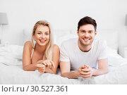 Купить «happy couple lying in bed at home», фото № 30527361, снято 25 февраля 2016 г. (c) Syda Productions / Фотобанк Лори