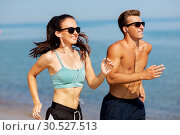 Купить «couple with earphones running along on beach», фото № 30527513, снято 1 августа 2018 г. (c) Syda Productions / Фотобанк Лори