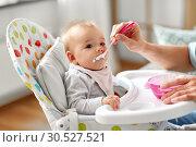 Купить «father feeding baby sitting in highchair at home», фото № 30527521, снято 25 августа 2018 г. (c) Syda Productions / Фотобанк Лори