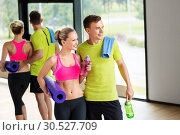 Купить «couple with bottles, exercise mat and towel in gym», фото № 30527709, снято 29 июня 2014 г. (c) Syda Productions / Фотобанк Лори
