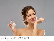 Купить «happy woman with perfume over gray background», фото № 30527869, снято 20 января 2019 г. (c) Syda Productions / Фотобанк Лори