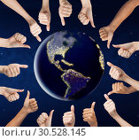 human hands showing thumbs up around earth planet. Стоковое фото, фотограф Syda Productions / Фотобанк Лори