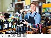 Купить «Man seller wearing apron having bottle of wine in hands», фото № 30528381, снято 25 мая 2019 г. (c) Яков Филимонов / Фотобанк Лори