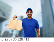 Купить «happy indian delivery man with food in paper bag», фото № 30528413, снято 12 января 2019 г. (c) Syda Productions / Фотобанк Лори