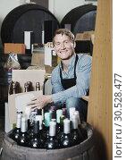 Купить «Man seller wearing apron having package box with wine bottles», фото № 30528477, снято 6 июня 2020 г. (c) Яков Филимонов / Фотобанк Лори