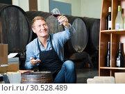 Купить «happy seller male wearing apron suggesting to try glass of wine», фото № 30528489, снято 6 июня 2020 г. (c) Яков Филимонов / Фотобанк Лори