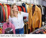 Купить «Positive girl looking for new leather jacket during shopping in retail shop», фото № 30528501, снято 5 сентября 2018 г. (c) Яков Филимонов / Фотобанк Лори