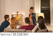 Купить «happy friends playing charades at home in evening», фото № 30528561, снято 22 декабря 2018 г. (c) Syda Productions / Фотобанк Лори