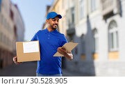Купить «delivery man with parcel and clipboard in city», фото № 30528905, снято 12 января 2019 г. (c) Syda Productions / Фотобанк Лори