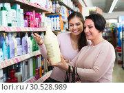 Купить «Women selecting hair care in store», фото № 30528989, снято 18 апреля 2019 г. (c) Яков Филимонов / Фотобанк Лори