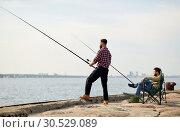 Купить «happy friends with fishing rods on pier», фото № 30529089, снято 8 сентября 2018 г. (c) Syda Productions / Фотобанк Лори