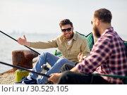 Купить «happy male friends with rods talking about fishing», фото № 30529105, снято 8 сентября 2018 г. (c) Syda Productions / Фотобанк Лори