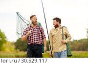 Купить «friends with fishing rods and net at lake or river», фото № 30529117, снято 8 сентября 2018 г. (c) Syda Productions / Фотобанк Лори