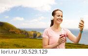 Купить «woman with smartphone and shake listening to music», фото № 30529129, снято 15 июня 2018 г. (c) Syda Productions / Фотобанк Лори