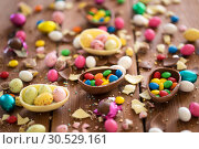 Купить «chocolate eggs and candy drops on wooden table», фото № 30529161, снято 15 марта 2018 г. (c) Syda Productions / Фотобанк Лори