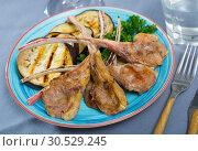 Купить «Grilled tasty lamb ribs with eggplants served at plate with greens», фото № 30529245, снято 15 июня 2019 г. (c) Яков Филимонов / Фотобанк Лори
