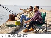Купить «happy friends with fishing rods on pier», фото № 30529277, снято 8 сентября 2018 г. (c) Syda Productions / Фотобанк Лори