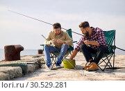 Купить «friends adjusting fishing rods with bait on pier», фото № 30529281, снято 8 сентября 2018 г. (c) Syda Productions / Фотобанк Лори