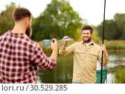 Купить «friend photographing fisherman with fish at lake», фото № 30529285, снято 8 сентября 2018 г. (c) Syda Productions / Фотобанк Лори