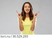 Купить «young woman or teenage girl with fingers crossed», фото № 30529293, снято 29 января 2019 г. (c) Syda Productions / Фотобанк Лори