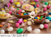 Купить «chocolate eggs and candy drops on wooden table», фото № 30529417, снято 15 марта 2018 г. (c) Syda Productions / Фотобанк Лори