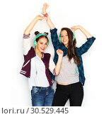 Купить «teenage girls in earphones listening to music», фото № 30529445, снято 19 декабря 2015 г. (c) Syda Productions / Фотобанк Лори